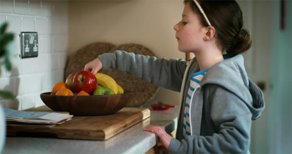 A healthy young girl takes a banana from a fruit bowl